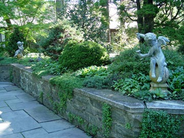 statues that add interest to a green planting at the New Jersey Botanical Garden.